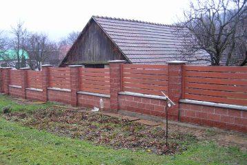 Ogrodzenia plastikowe do ogrodu połaczone ze słupkami z cegły. Zdjęcie ze strony https://ogrodzeniaplastikowe.pl/galeria-ogrodzen-everwood/
