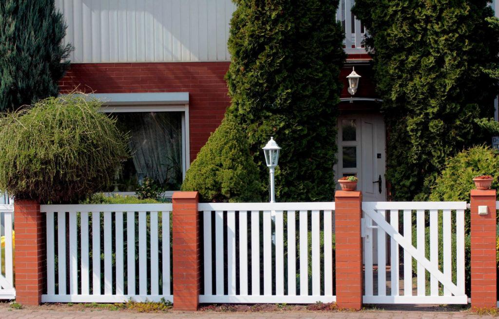 Sztachety plastikowe wykorzystane jako furtka i ogrodzenie ze słupkami z czerwonej cegły. Obraz za https://ogrodzeniaplastikowe.pl/galeria-ogrodzen-ecowood/